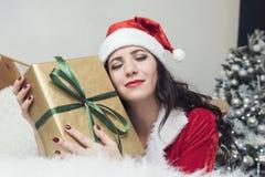 Усмехаясь девочка-подросток в шляпе хелпера santa с много подарочных коробок на белой предпосылке Положительная эмоциональная дев стоковые фото
