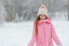 Усмехаясь девушка в водовороте снежинок Стоковая Фотография
