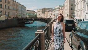Усмехаясь девушка в запятнанном платье смотрит в небо около реки в старом центре города акции видеоматериалы