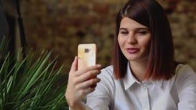 Усмехаясь девушка в кафе говоря на видео- болтовне на умном телефоне пока выпивающ кофе акции видеоматериалы