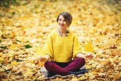 Усмехаясь девушка в осени сидя на траве и держать 2 желтых листь в руках Стоковая Фотография RF