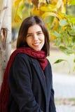 Усмехаясь девушка в парке в осени стоковая фотография