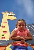 Усмехаясь девушка в парке потехи Стоковая Фотография