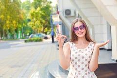 Усмехаясь девушка держа ключи показывая здание стоковые фотографии rf