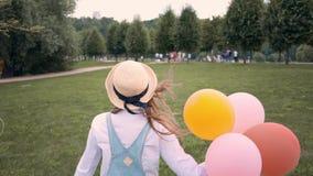 Усмехаясь девушка имбиря в солнечных очках бежать и завихряясь с воздушными шарами в парке акции видеоматериалы