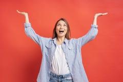 Усмехаясь девушка имея потеху на красной предпосылке держа руки вверх по усмехаться признательно стоковое изображение