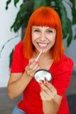 Усмехаясь девушка используя губную помаду дома Стоковая Фотография