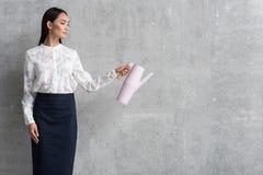 Усмехаясь девушка карьеры держа чайник в руке Стоковые Фото