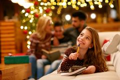 Усмехаясь девушка лежа и пишет письмо в Санта Клауса для Christma стоковая фотография