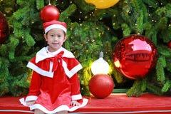 Усмехаясь девушка маленького ребенка в костюме Санта с предпосылкой рождества праздники рождества счастливые веселые стоковое фото
