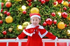Усмехаясь девушка маленького ребенка в костюме Санта с предпосылкой рождества праздники рождества счастливые веселые стоковые фотографии rf