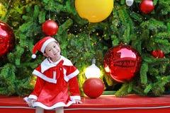 Усмехаясь девушка маленького ребенка в костюме Санта с предпосылкой рождества праздники рождества счастливые веселые стоковое фото rf
