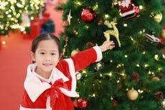 Усмехаясь девушка маленького ребенка в костюме Санта с предпосылкой рождества праздники рождества счастливые веселые стоковая фотография rf
