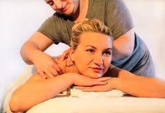Усмехаясь девушка наслаждается на таблице массажа Стоковое фото RF