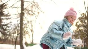 Усмехаясь девушка наслаждаясь холодным солнечным утром в парке Веселая активная школьница бросает снежный ком на камеру имея видеоматериал