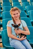 Усмехаясь девушка ослабляя с собакой ребенок девушки на местах стадиона Стоковая Фотография