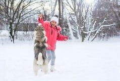Усмехаясь девушка подает осиплая собака в сельской местности в стоковое фото rf