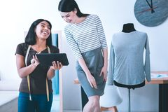 Усмехаясь девушка показывая что-то на ее планшете к ее другу стоковое фото rf