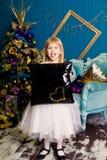 Усмехаясь девушка с подушкой против предпосылки рождественской елки стоковое изображение