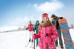 Усмехаясь девушка с семьей на местности лыжи стоковое изображение
