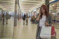 Усмехаясь девушка с хозяйственными сумками в торговом центре Стоковые Фотографии RF