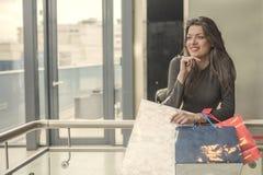Усмехаясь девушка с хозяйственными сумками в торговом центре Стоковые Фото