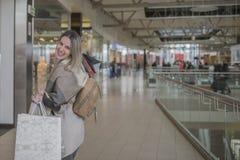 Усмехаясь девушка с хозяйственными сумками в торговом центре Стоковое Изображение RF