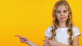 Усмехаясь девушка указывая пальцы на пустой космос на желтой предпосылке, шаблоне акции видеоматериалы