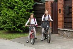 2 усмехаясь девушки в школьной форме ехать к школе на велосипедах Стоковое фото RF