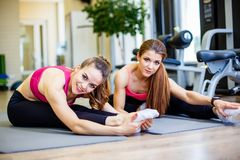 2 усмехаясь девушки делают протягивать тренировки в спортклубе Стоковые Изображения RF