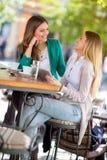Усмехаясь девушки сидя на кафе и наслаждаться Стоковые Изображения