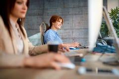 Усмехаясь дизайнер женщины на работе работая на компьютере для нового proje стоковые изображения