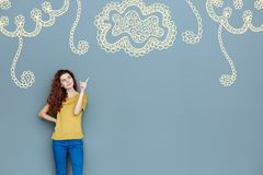 Усмехаясь дизайнер указывая к стене пока показывающ орнамент цветка Стоковые Изображения