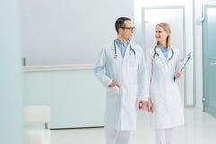 2 усмехаясь доктора в белых пальто с стетоскопами и диагнозом Стоковые Фото