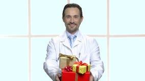 Усмехаясь доктор представляя подарочные коробки акции видеоматериалы