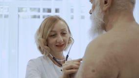 Усмехаясь доктор слушает сердце eldelry человека с стетоскопом сток-видео