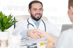 Усмехаясь доктор тряся руки с женским пациентом в офисе Стоковое Изображение