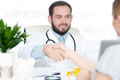 Усмехаясь доктор тряся руки с женским пациентом в офисе Стоковые Изображения RF