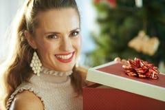 Усмехаясь домохозяйка около подарка рождества рождественской елки раскрывая стоковые фото