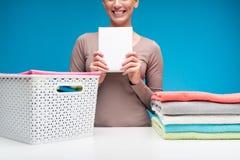 Усмехаясь домохозяйка с пакетом стирального порошка Стоковая Фотография