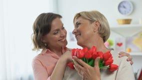 Усмехаясь дочь обнимая старшую мать держа тюльпаны подарок, приветств видеоматериал