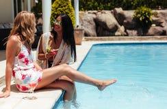 Усмехаясь друзья беседуя на poolside Стоковое фото RF