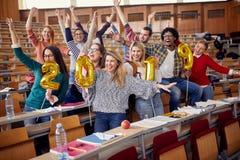 Усмехаясь друзья имея партию в университете стоковые изображения rf