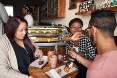 Усмехаясь друзья сидя на кафе ставят есть на обсуждение десерты совместно стоковые фото