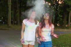 2 усмехаясь друз имея потеху с краской Holi в парке Стоковое Фото