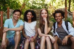4 усмехаясь друз сидя на лестницах в лесе Стоковое Изображение RF