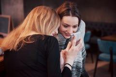 2 усмехаясь друз читая смешную онлайн болтовню на современном телефоне сидя с вкусным кофе в ресторане Девушки битника Стоковая Фотография RF
