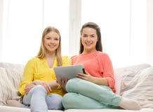 2 усмехаясь девочка-подростка с ПК таблетки дома Стоковые Фото