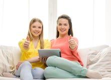 2 усмехаясь девочка-подростка с ПК таблетки дома Стоковое Изображение RF