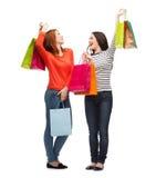 2 усмехаясь девочка-подростка с хозяйственными сумками Стоковая Фотография RF